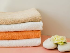 close-up-folded-clean-towels-with-flower_23-2148230616
