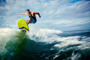 An image showing a man surfing the waves.